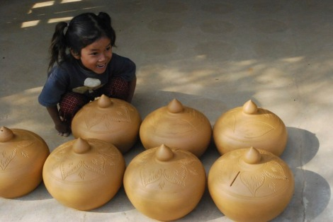 A little girl helps her Mum with the pottery
