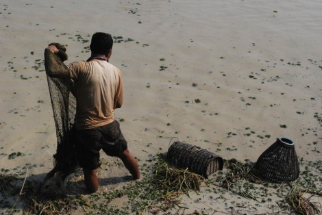 Fishing by hand in a muddy pond, Cambodia